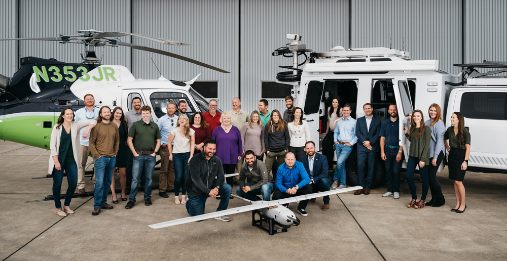 A group of people standing in front of a helicopter and a truck