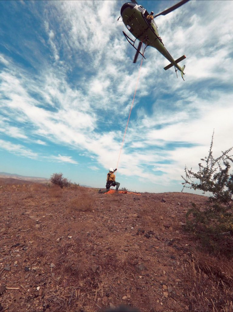 A helicopter hovering above a USFS worker
